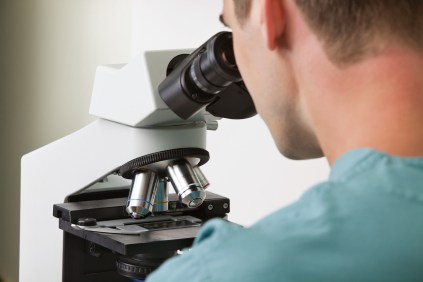 A doctor looking into a microscope